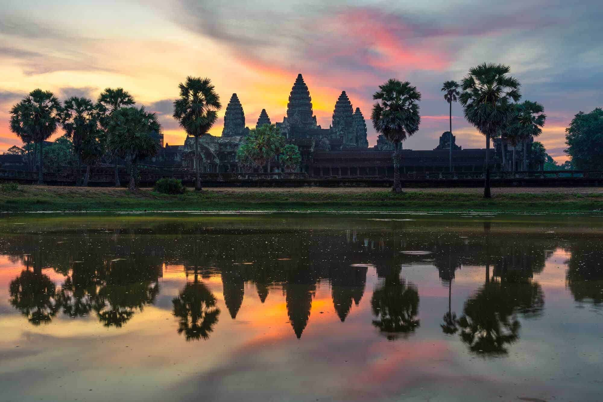 A photo of Angkor Wat Temple at sunrise reflected in water.