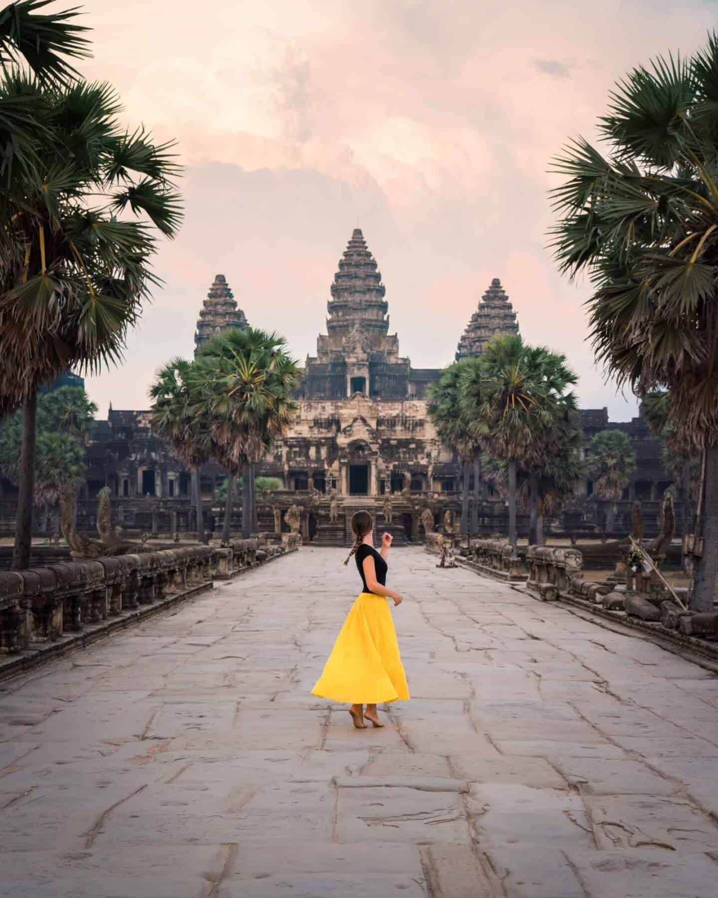 A sunset photo of the Angkor Wat Temple featuring @travelsofsophie in a bright yellow dress.
