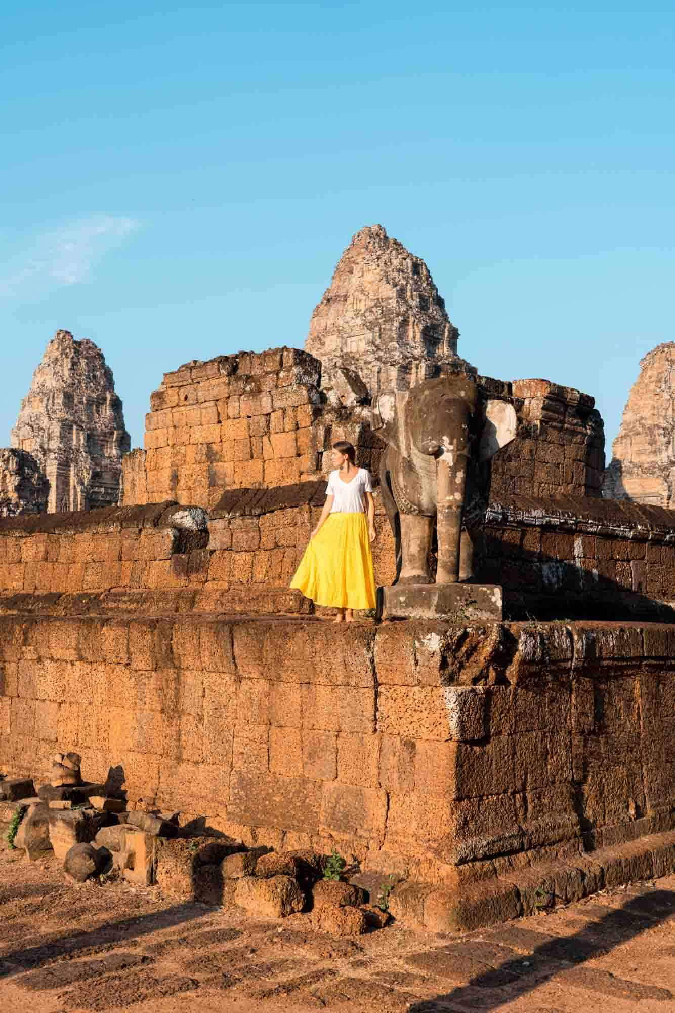 A girl standing next to an elephant sculpture at East Mebon temple Angkor Wat Cambodia