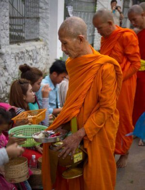 A buddhist monk receiving alms in Luang Prabang Laos