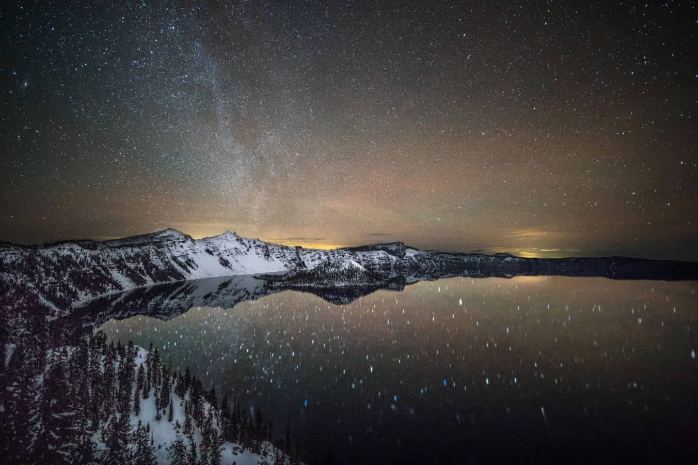 Star filled astrophotography photo of Crater Lake National Park at night.