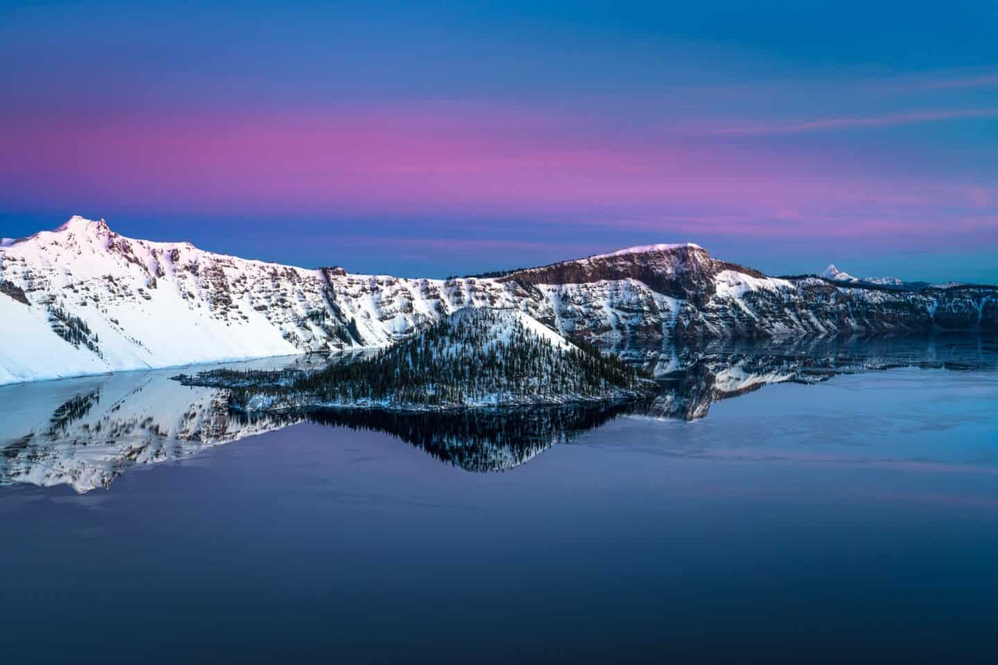 Wizard Island decorated in blue and purple tones, photographed on a snowy winter sunrise.