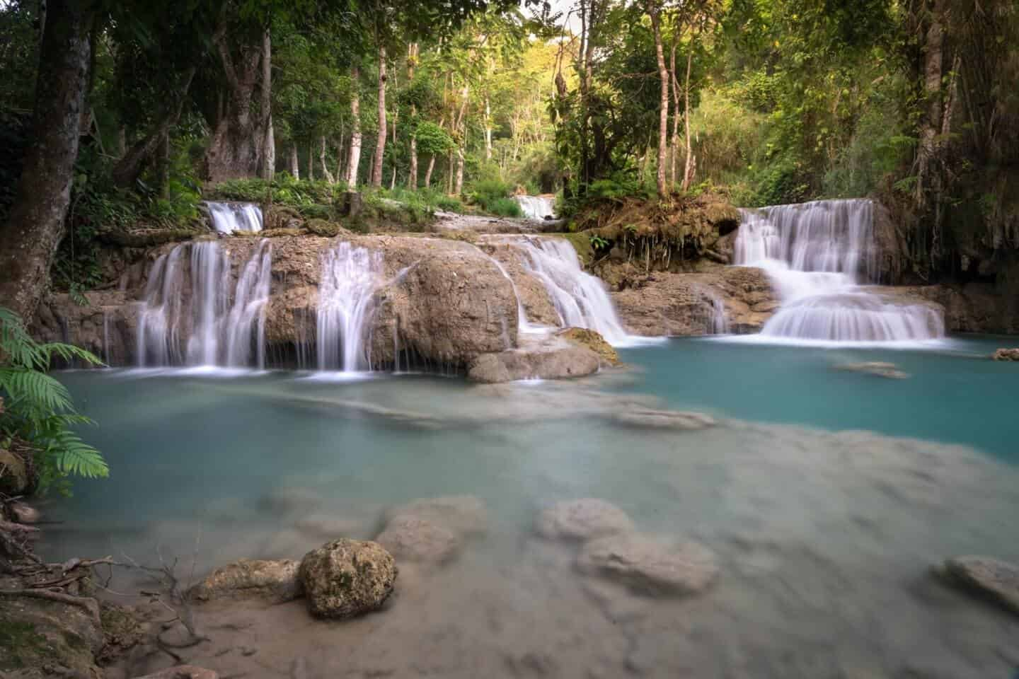 Even light on first pools of Kuang Si Falls, while the surrounding foliage bathes in the warm light of morning.