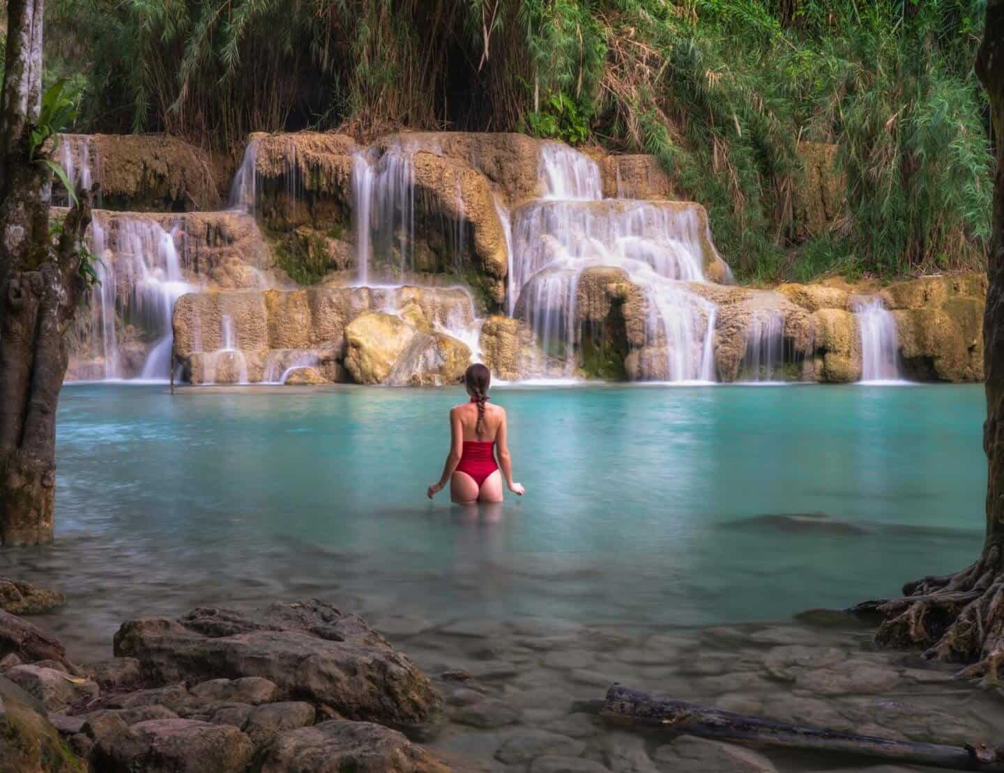 Travels of Sophie wades through the stunning turquoise waters of Kuang Si Falls.