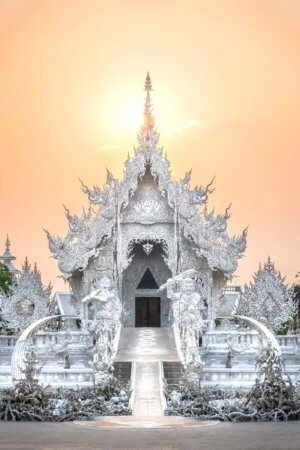 Golden light of sunset fills the sky at the White Temple in Chiang Rai, Thailand.