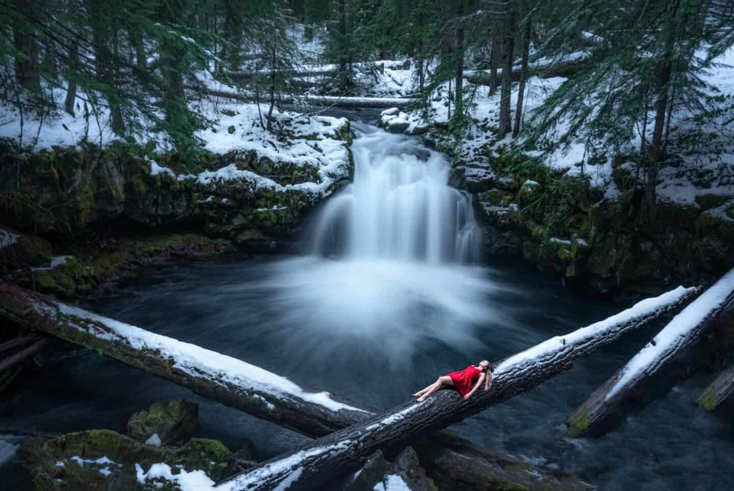Winter photography featuring Travels of Sophie in a red dress in front of Whitehorse Falls in Southern Oregon.