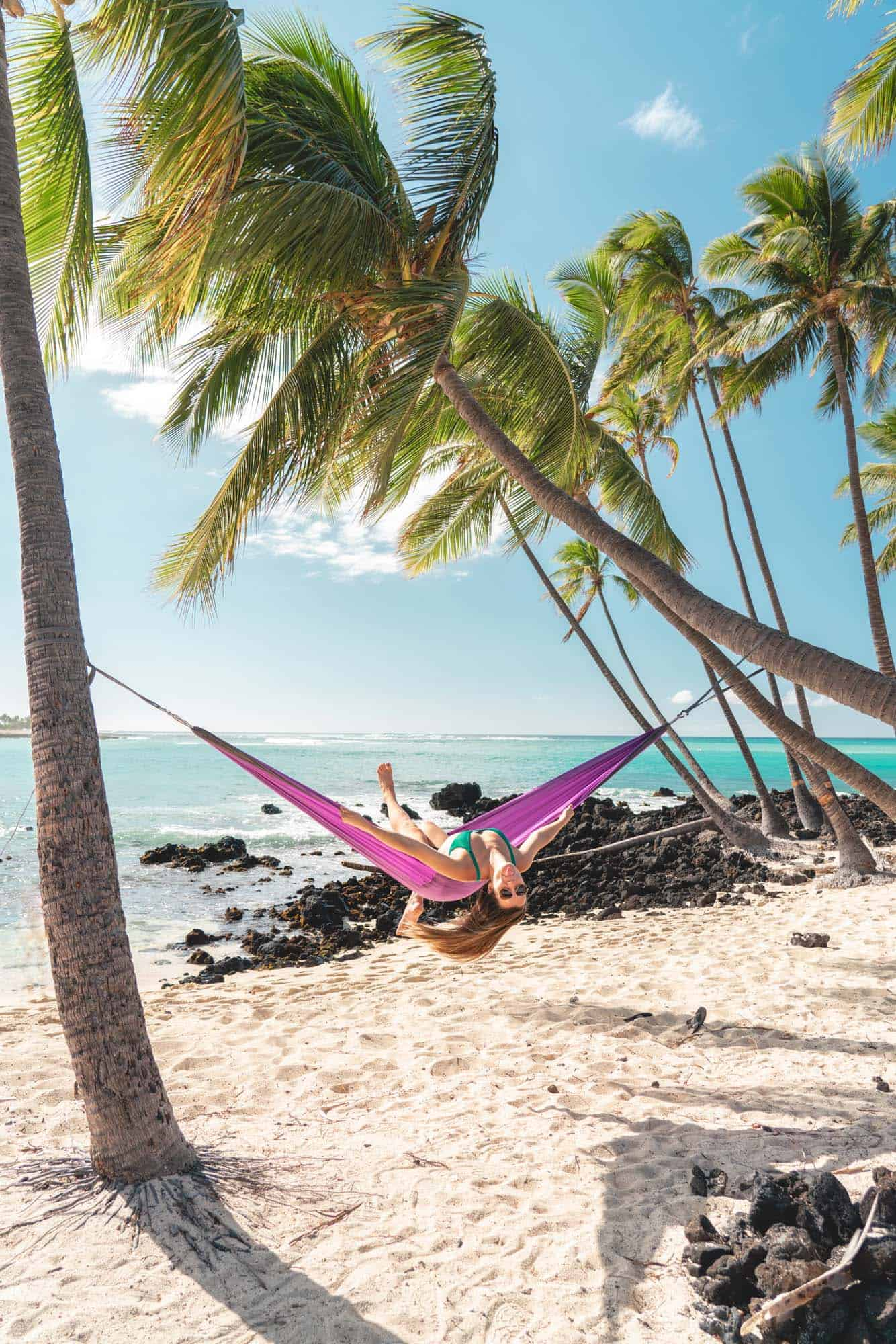 Sophie swings from a hammock in the postcard-perfect scene at Mahaiula Beach.