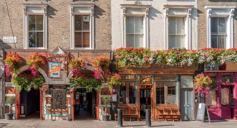 Flowers adorn the front of restaurants along Portobello Road, Notting Hill, London