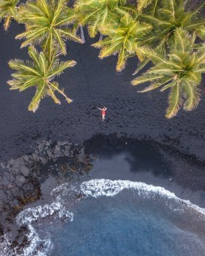 Aerial photo of a girl under palm trees on Punalu'u Black Sand Beach in Hawaii