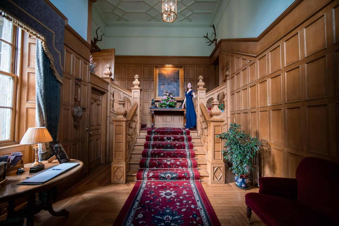 Travels of Sophie coming down the carpeted stairs of the welcoming parlour at Glenapp Castle