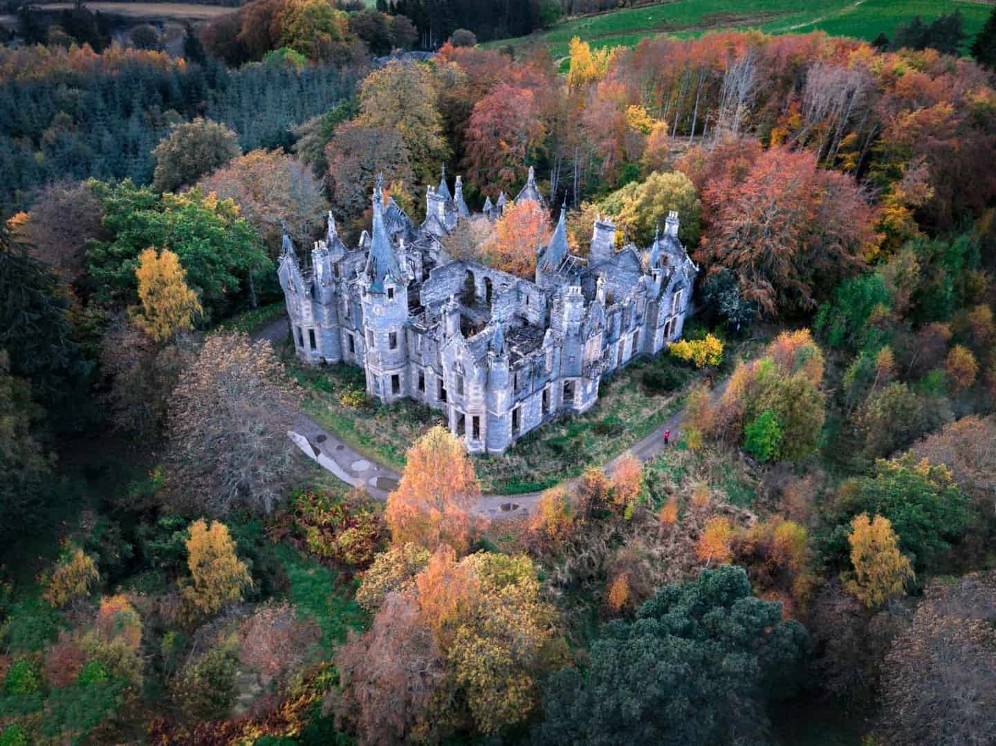 Best castle in Scotland: Dunalistair Castle seen from a drone surrounded by autumn colours.
