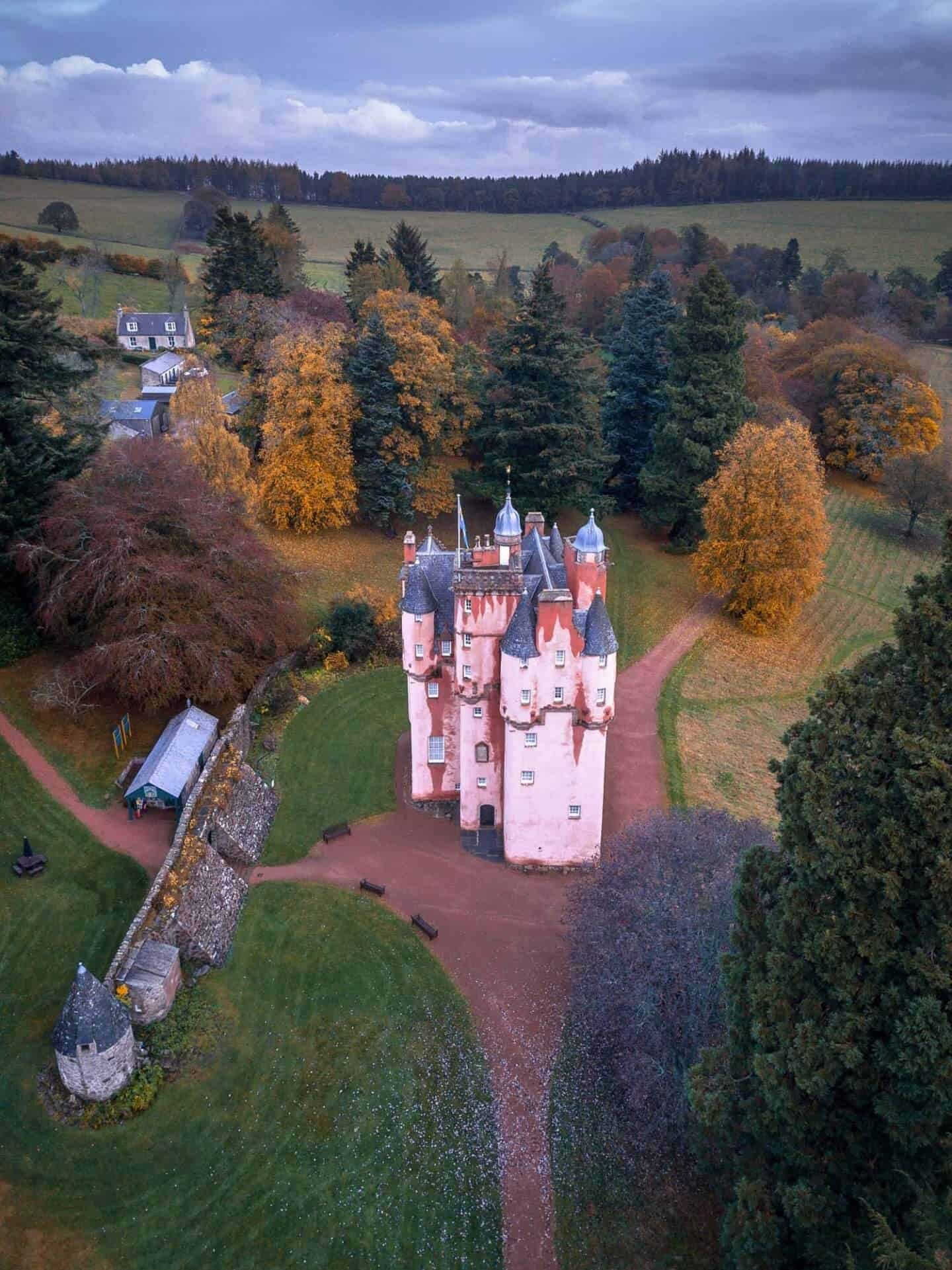 Craigievar Castle as viewed from above with autumn foliage surrounding it.