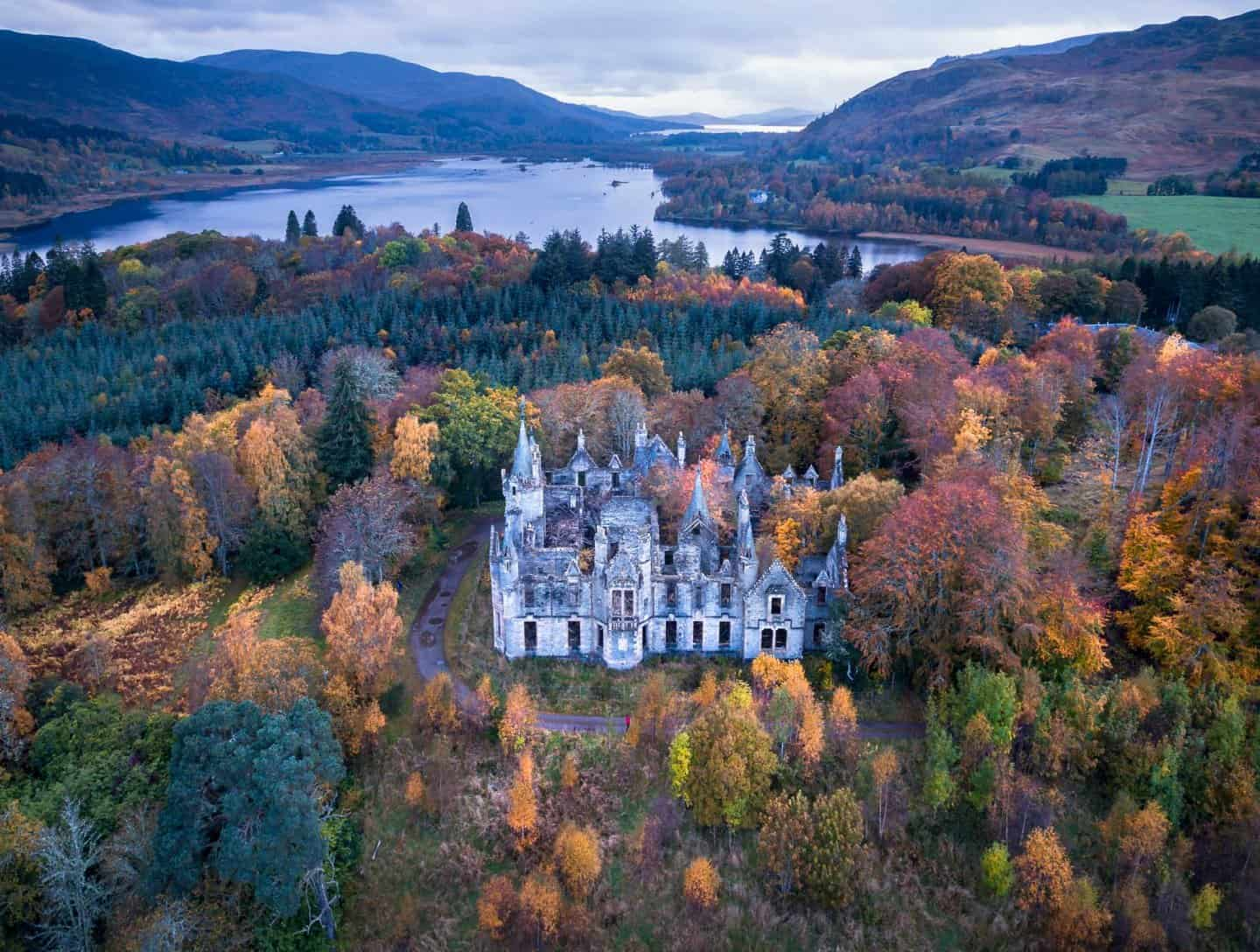 Dunalastair Castle surrounded by fall foliage.