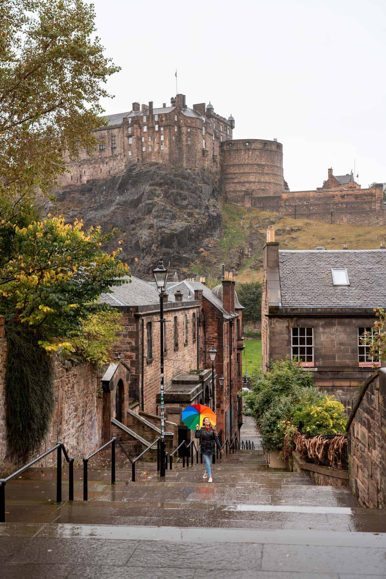 A young girl with a colorful rainbow walks up the steps of the Vennel in Edinburgh.