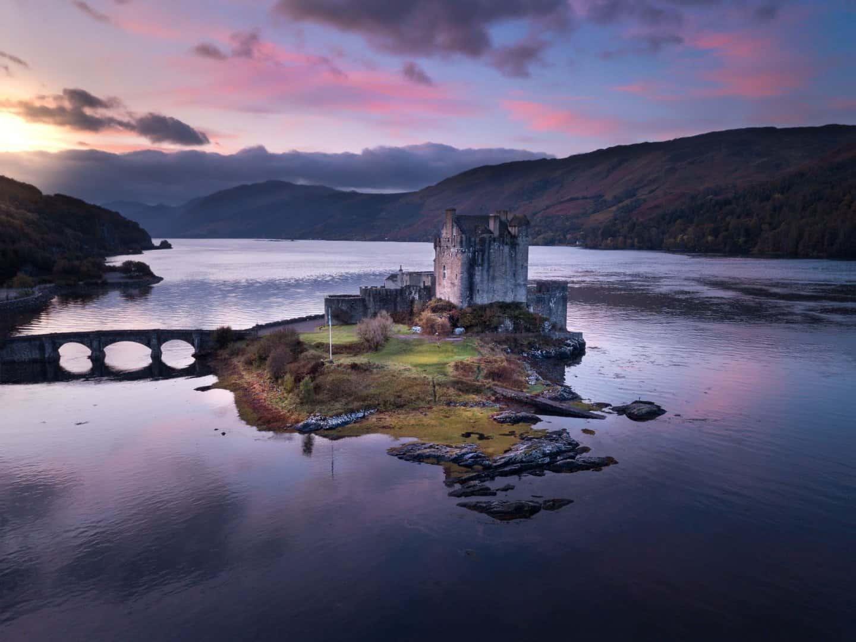 Best castles in Scotland: A drone photo capturing Scotland's best castle, Eilean Donan, at sunrise.