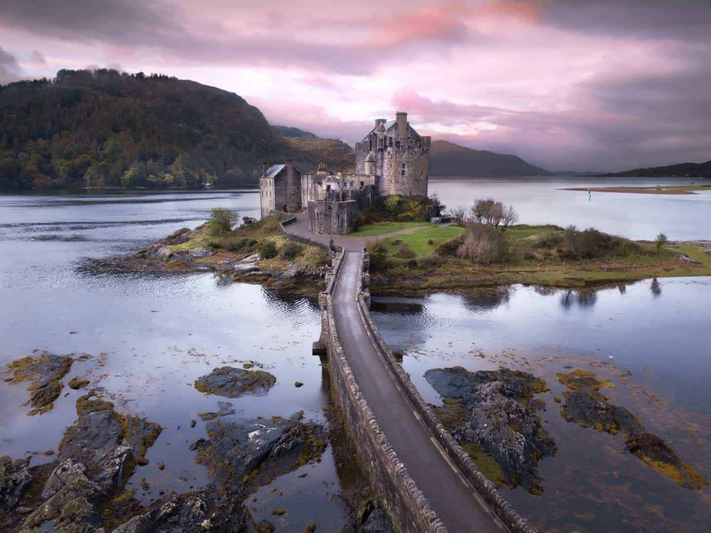 A pink sky sunrise at the most famous and best castle in Scotland, Eilean Donan Castle.
