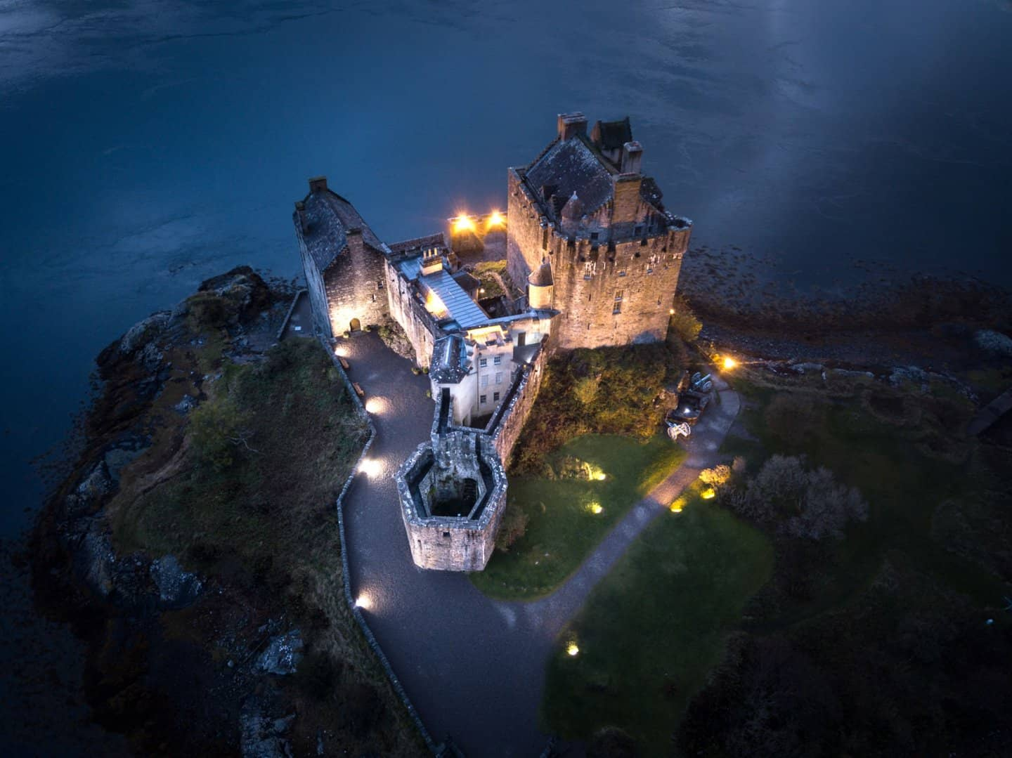 Looking down at Eilean Donan Castle at night from a drone.