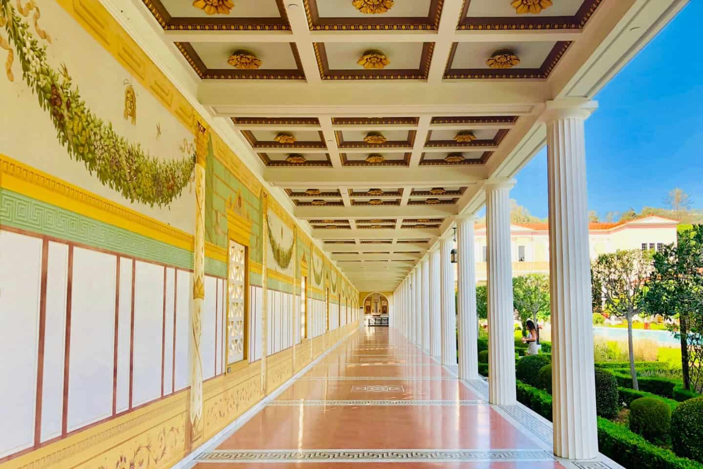 A beautiful walkway aligned with columns at the Getty Villa - a must on your Los Angeles bucket list