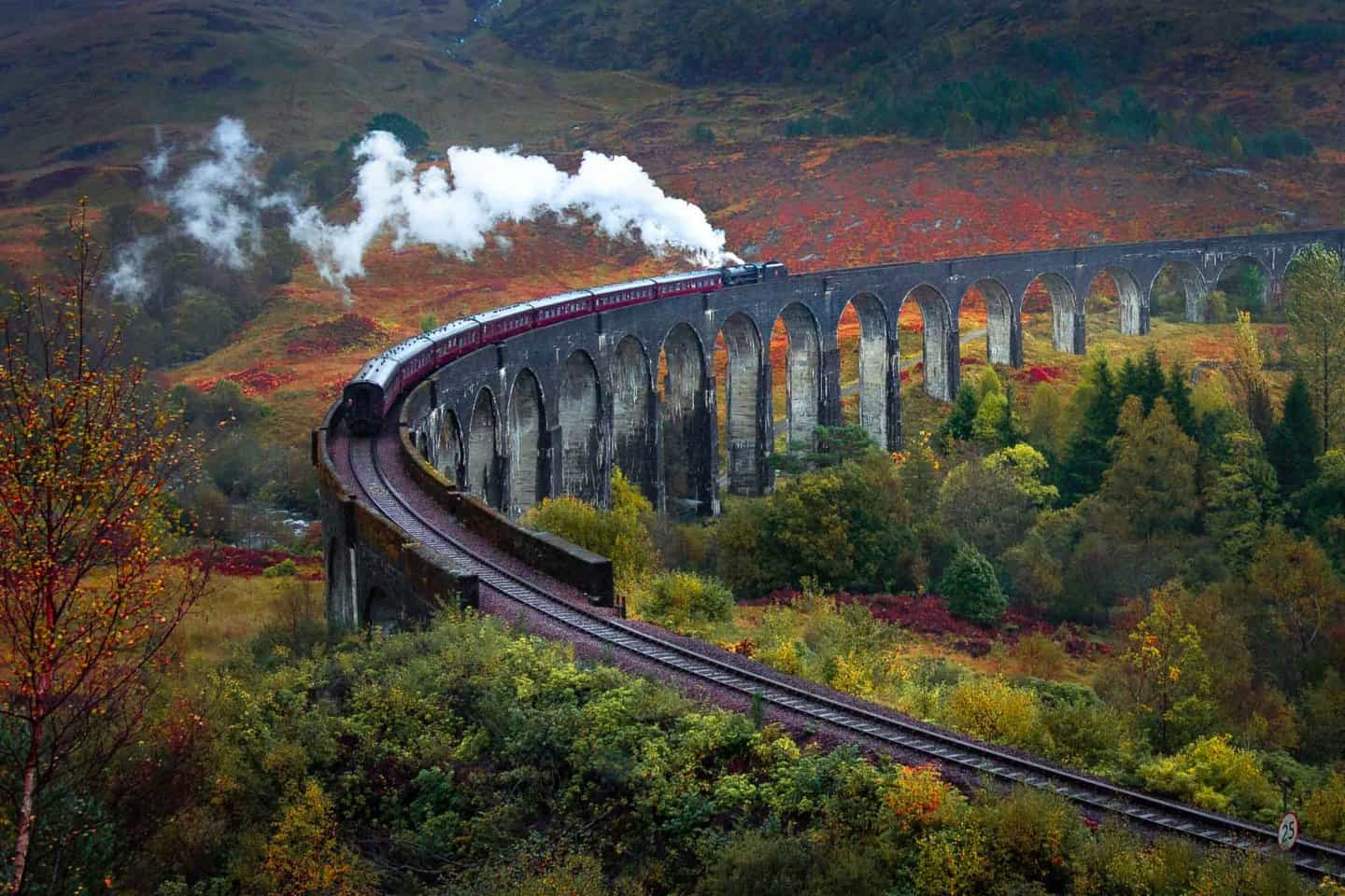 The magical Harry Potter train at Glenfinnan Viaduct rolls through this Autumn scene.