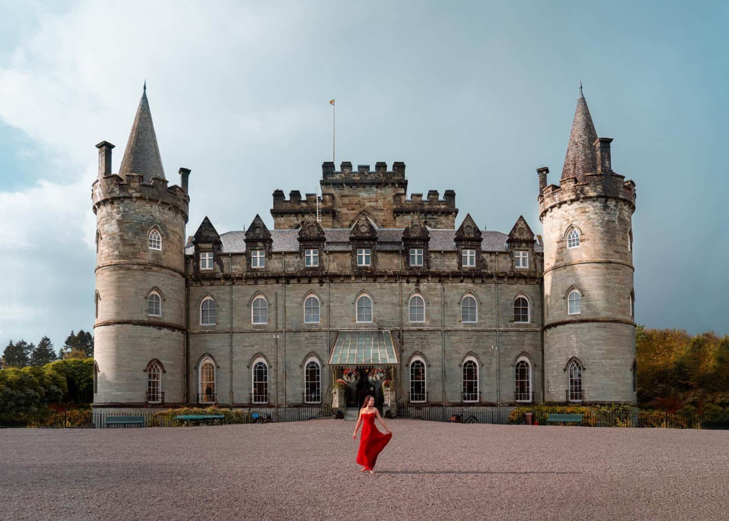 A real life princess in a red dress poses in front of Inveraray Castle in Scotland.