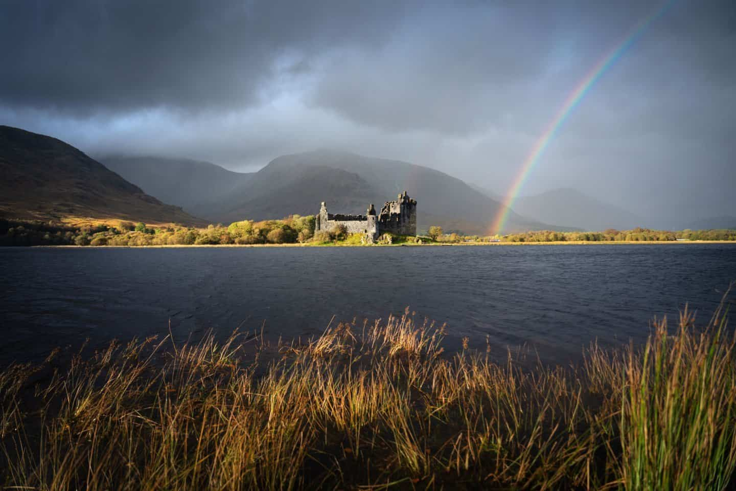 A breathtaking burst of light hits Kilchurn Castle while an autumn rainbow ignites in color.