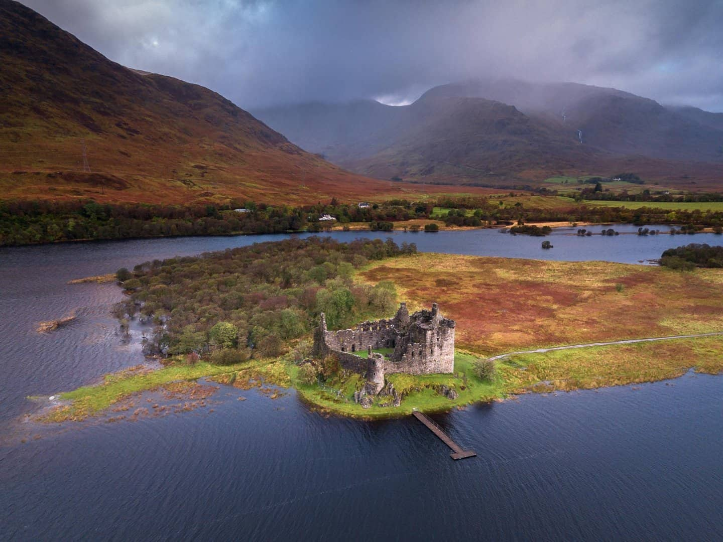 A drone photo of Kilchurn Castle surrounded by amazing autumn color.