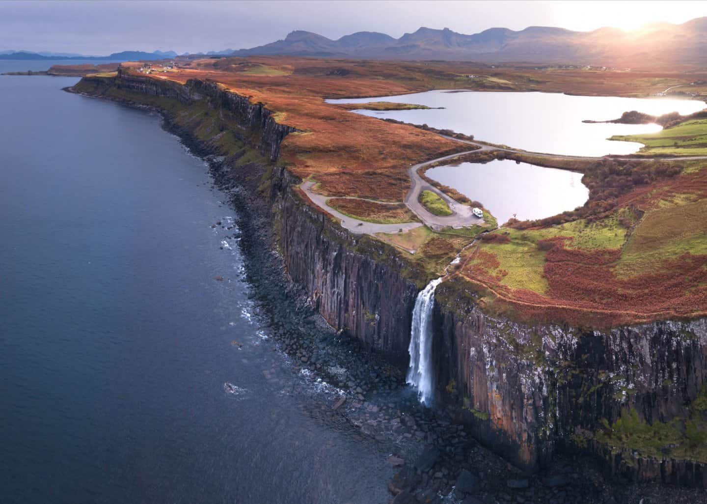 A drone shot reveals the landscape from high above Kilt Rock on the best Scotland road trip itinerary.