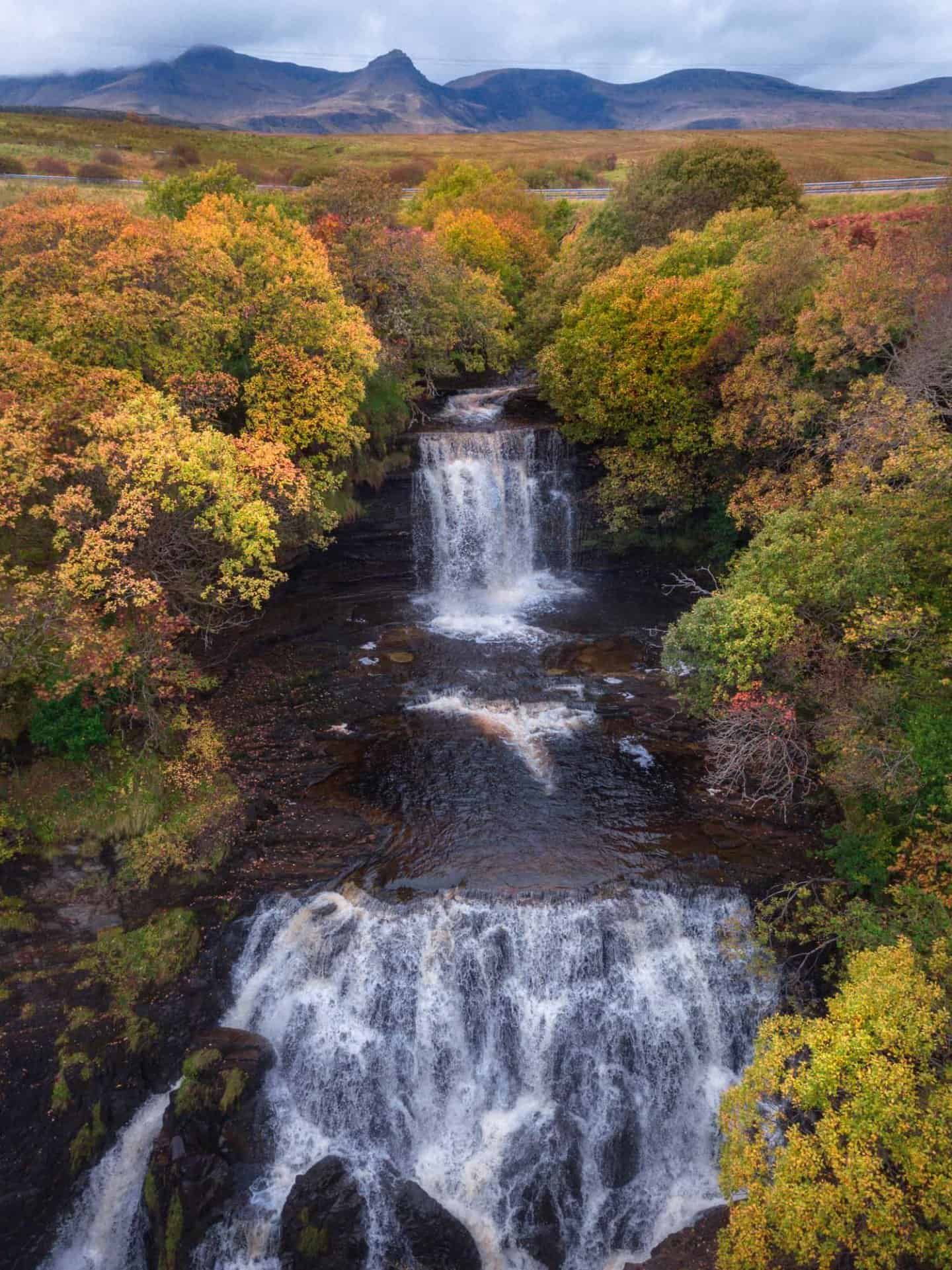 A roadside pull off on the best Scotland road trip itinerary allows access to Lealt Falls, seen tucked into the fall foliage of Isle of Skye.