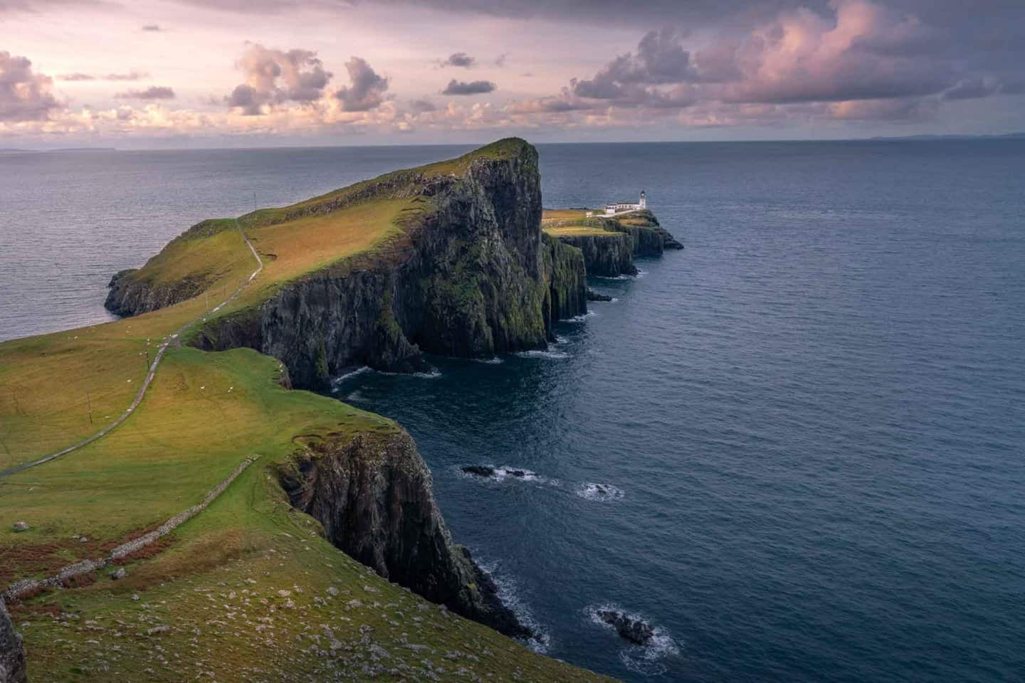 Neist Point Lighthouse on the Isle of Skye bathes in the glow of sunrise.