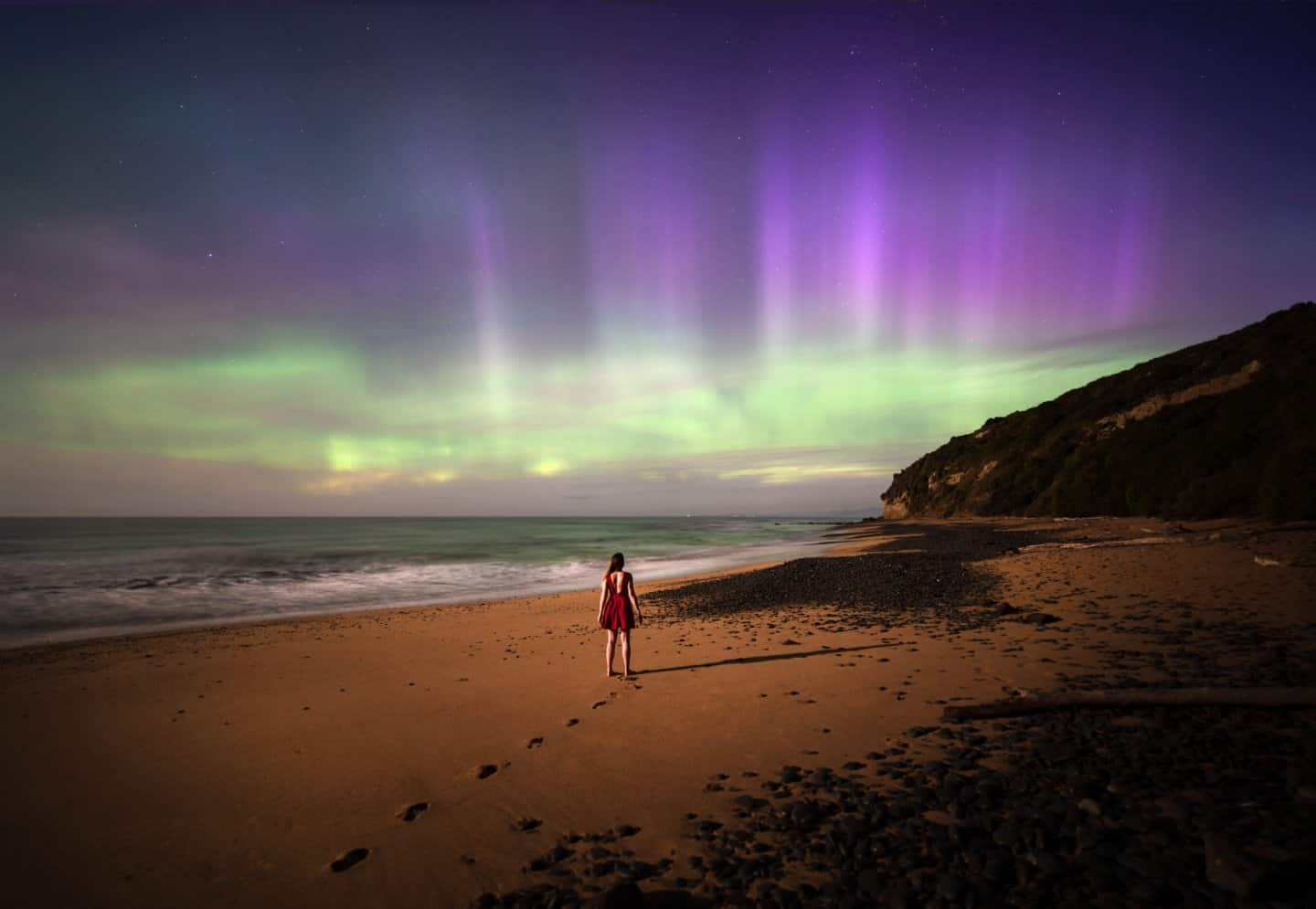 On a beach in New Zealand witnessing the rare Aurora Australis, aka Southern Lights, on a moonlit night.