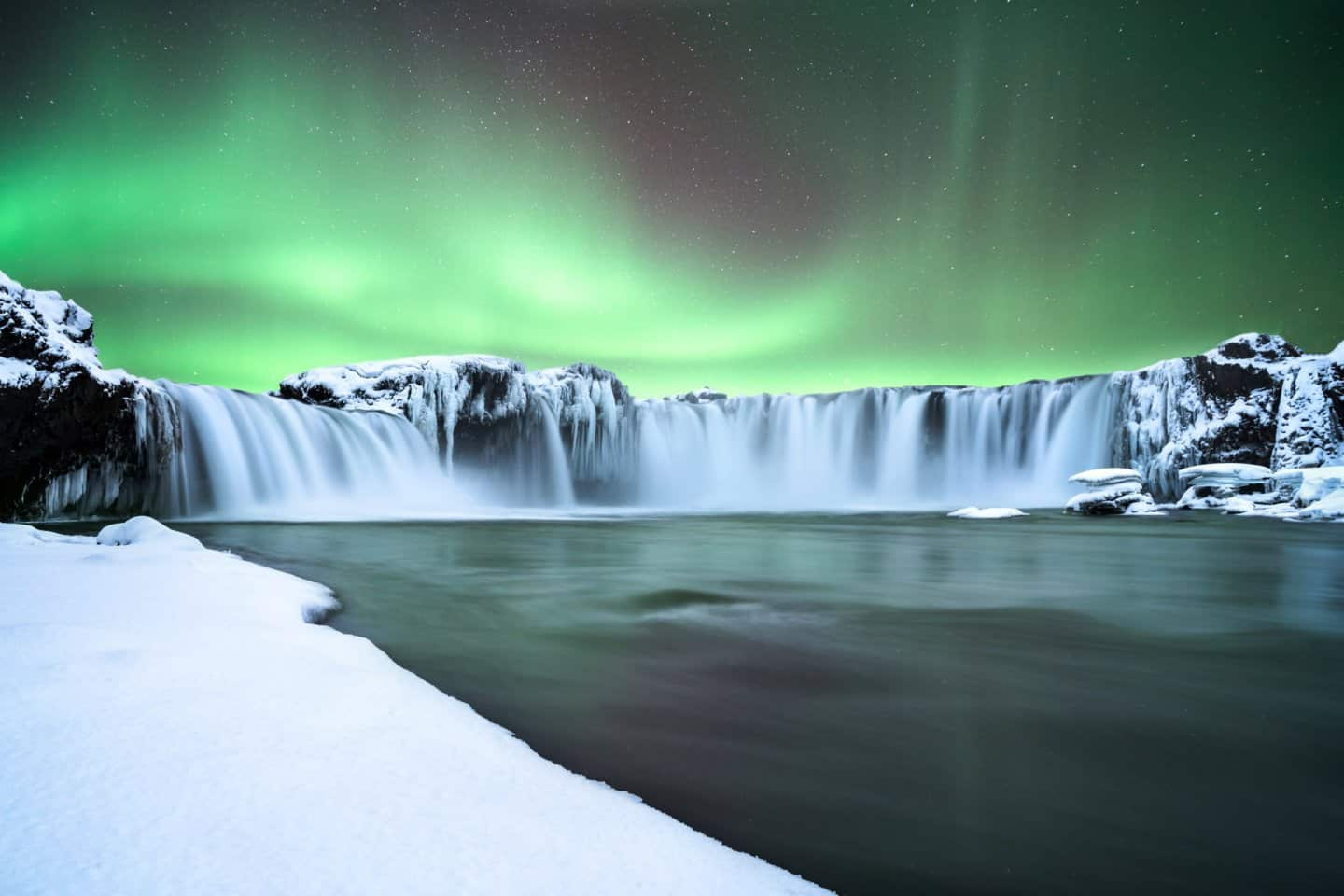 Photographing aurora at Godafoss waterfall in Iceland.