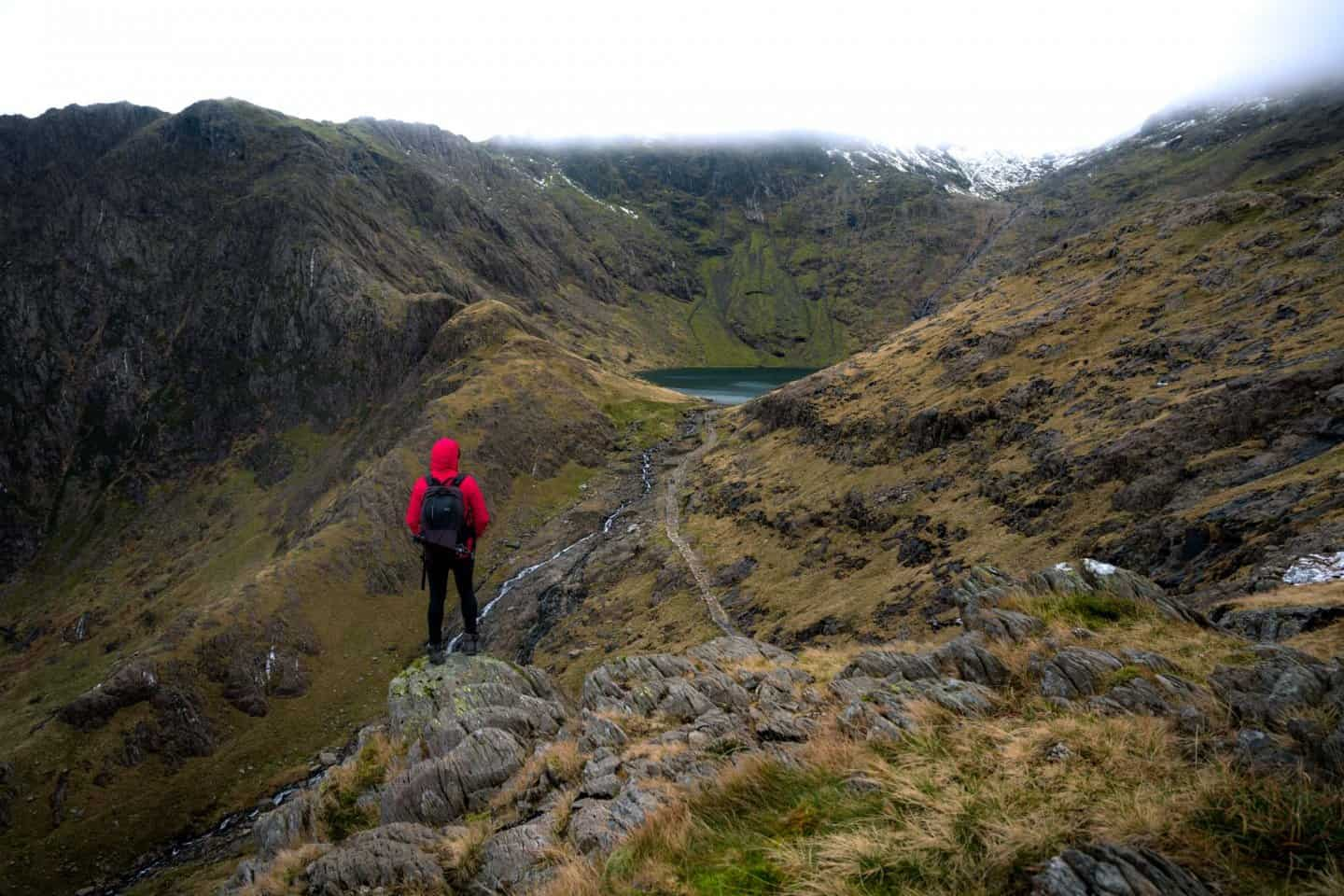 My partner Adam (WeOwntheMoment Photography) observing Llyn Glaslyn and a cloud-covered Snowdon Peak.