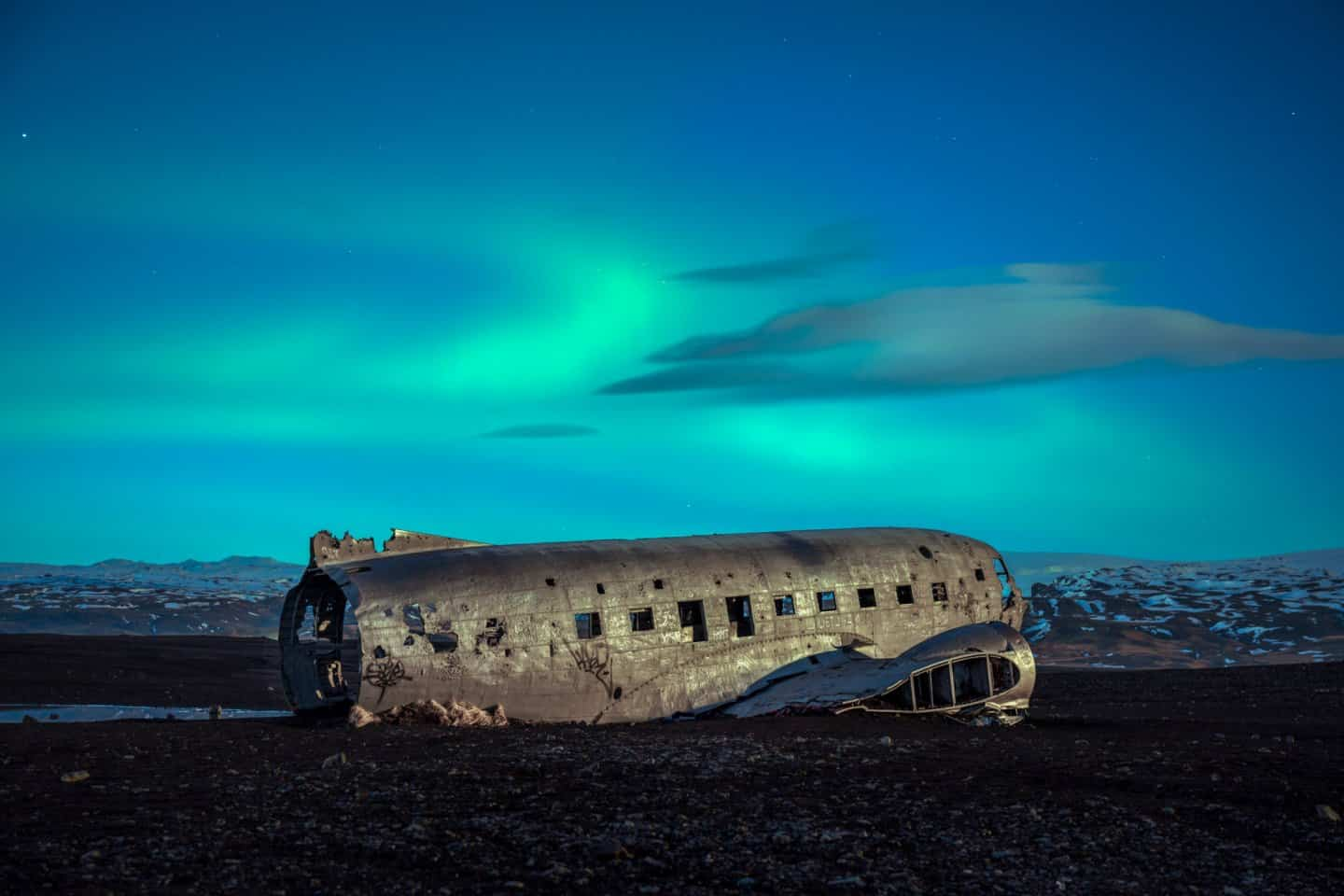 Photographing aurora at the DC plane wreck under the light of a full moon.