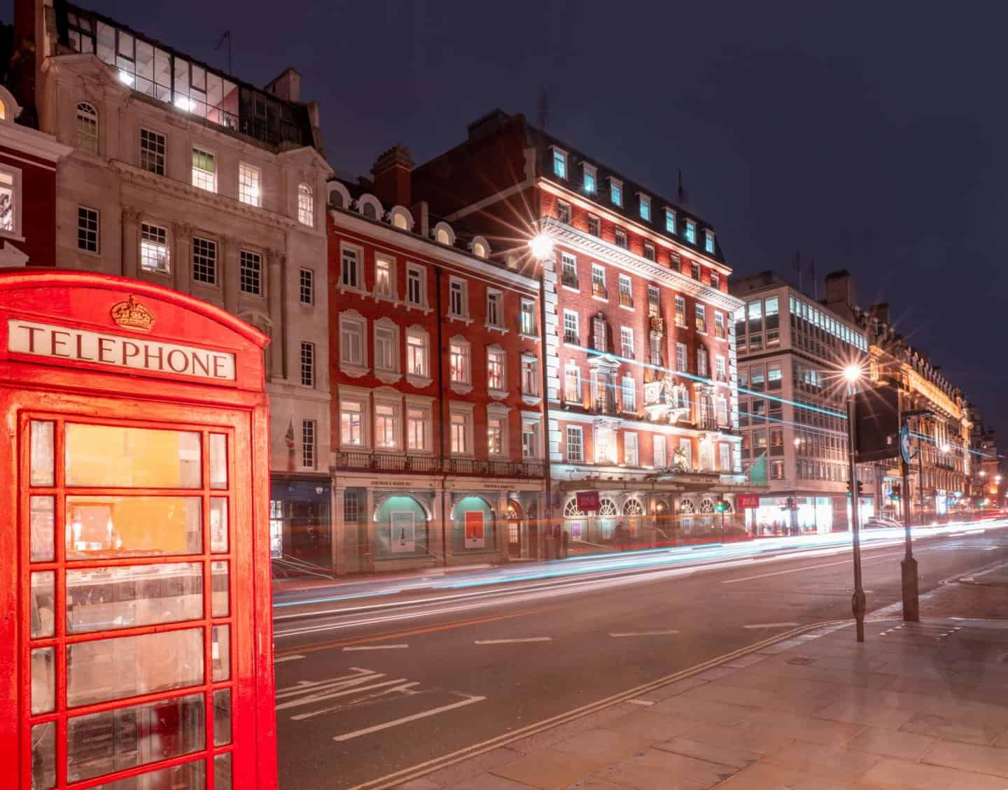 Fortnum and Mason at night, behind a red London phone box, on Piccadilly Street, one of the most famous streets in London