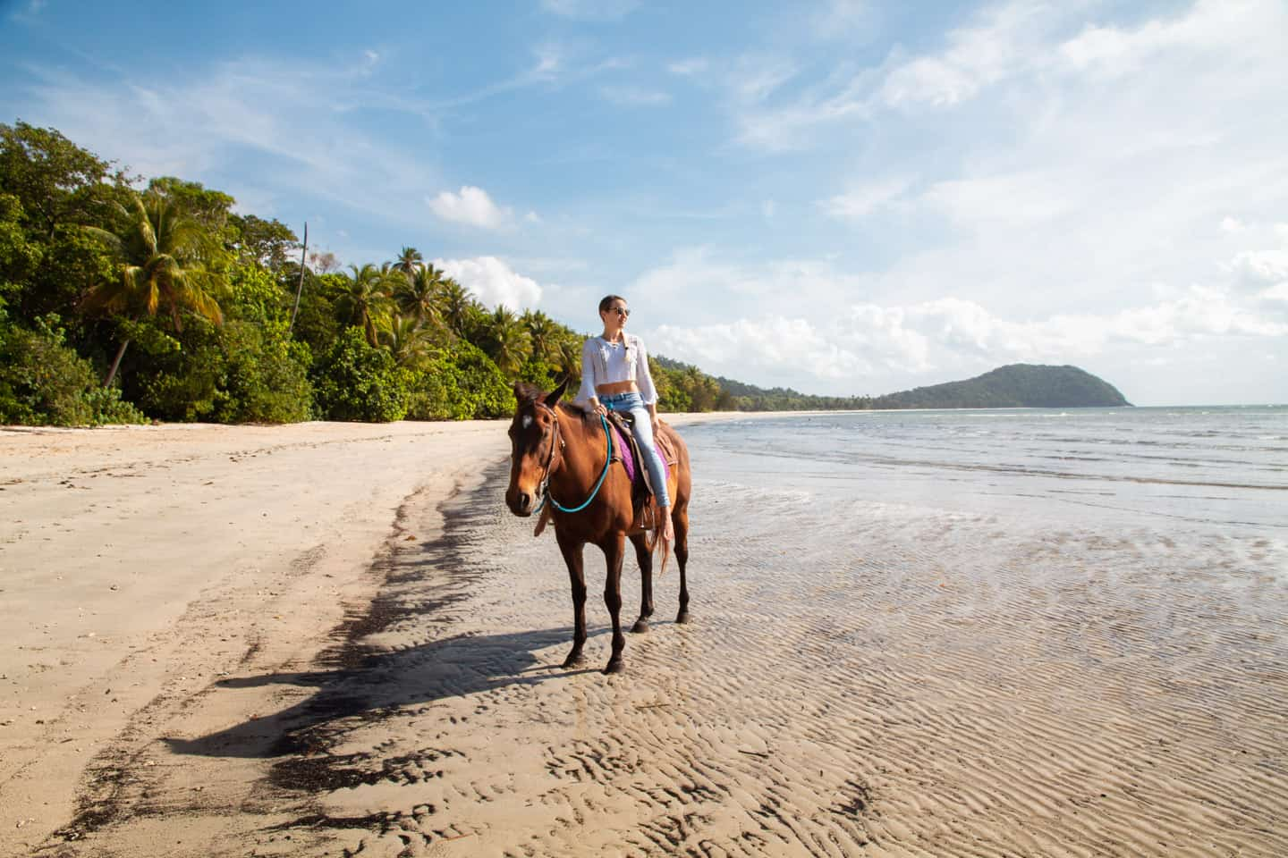 A girl horse riding on the beach at Cape Tribulation Daintree Australia