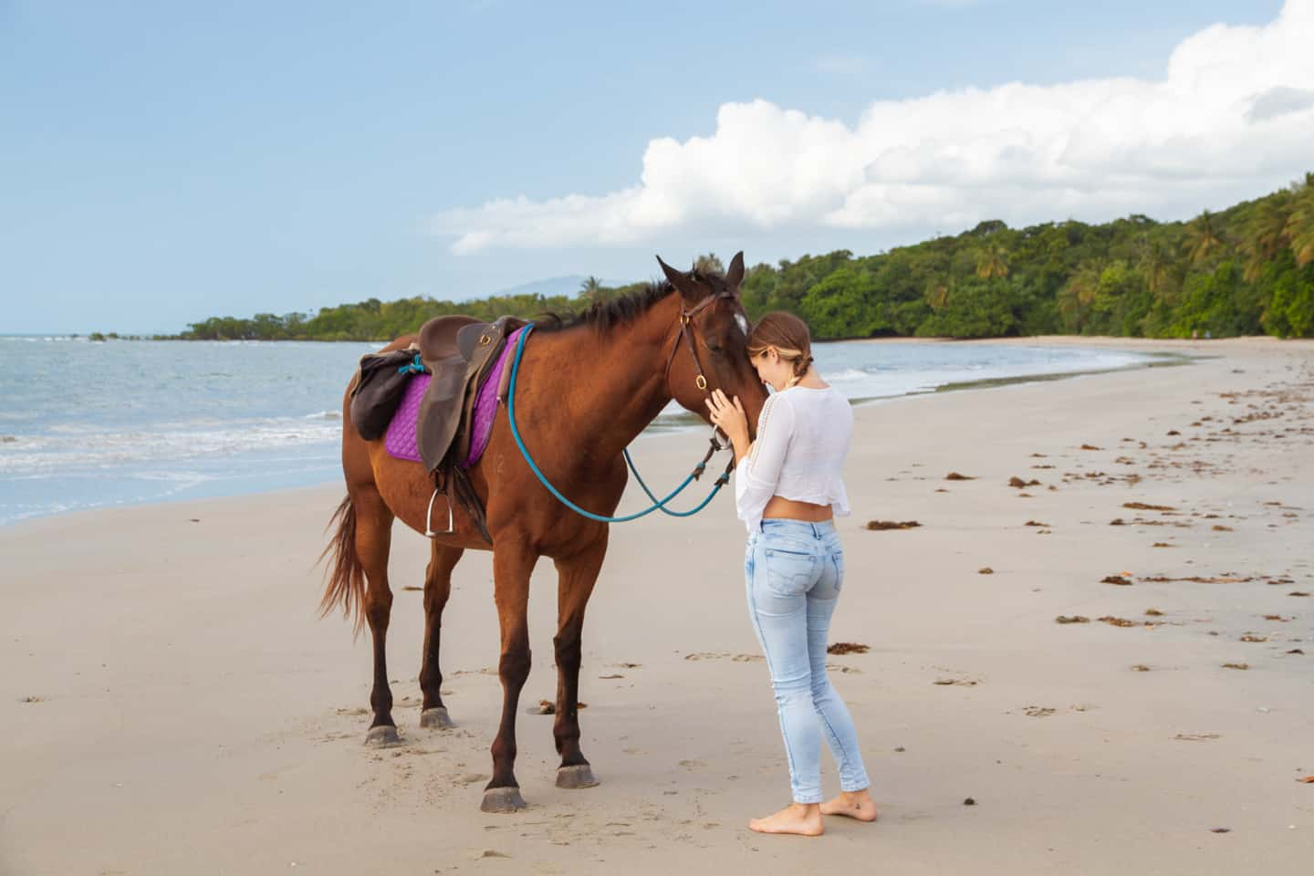 A girl and horse on the beach at Cape Tribulation Daintree