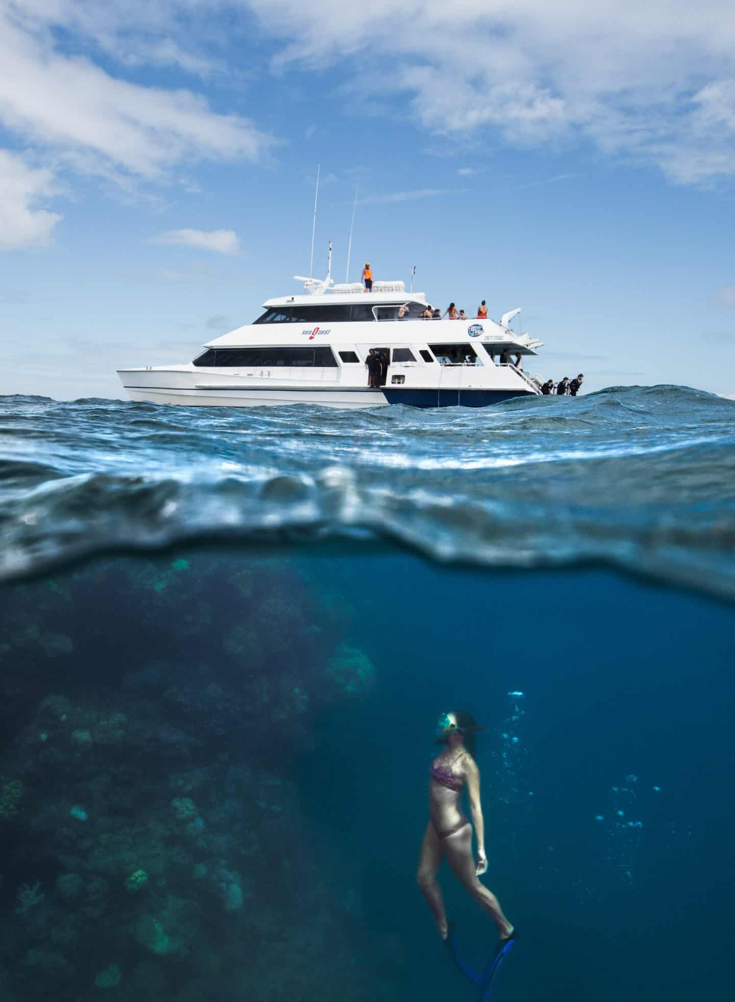 an over under photo of a girl free diving beneath a boat on the Great Barrier Reef Australia
