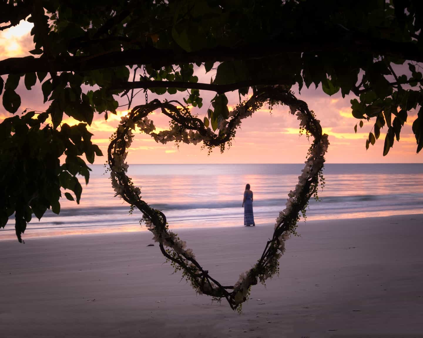 A girl framed in a heart watching the sunrise on the beach at Cape Tribulation, Daintree.