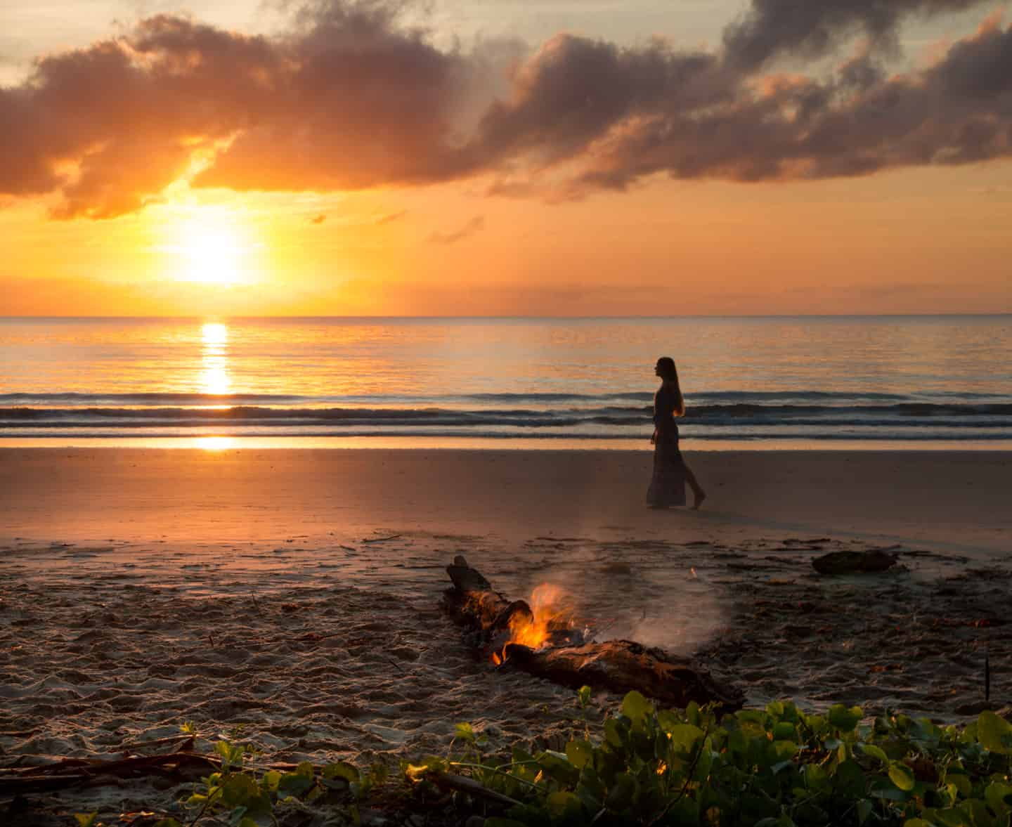 A girl walking along Four Mile Beach at sunrise