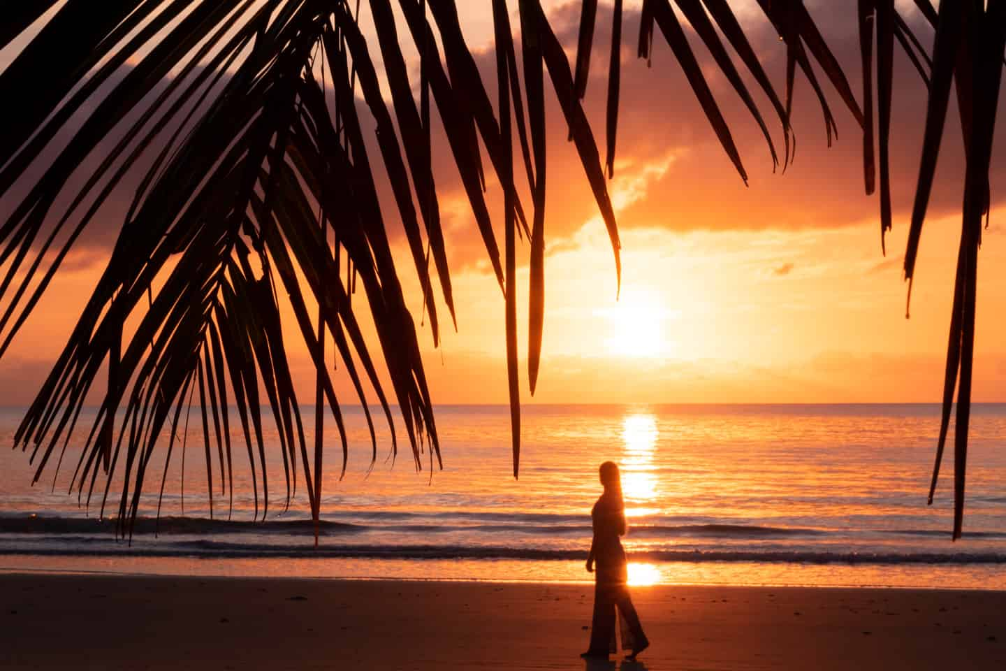 A girl silhouetted against the rising sun over the water on Four Mile Beach Cairns Australia
