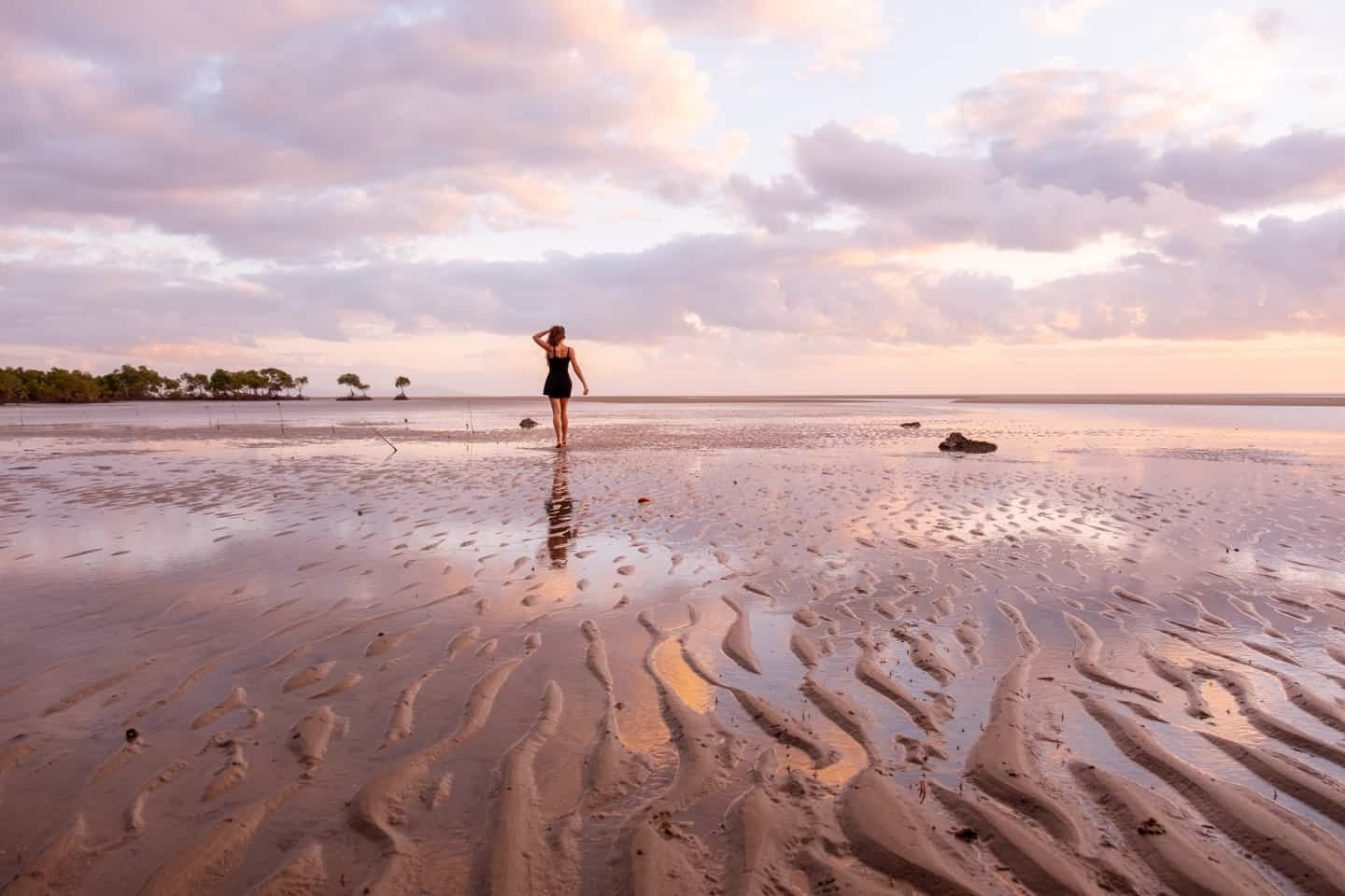 An image of a girl walking along the sand at Yule Point, Port Douglas at sunrise with the sunrise reflecting on the wet rippled sand