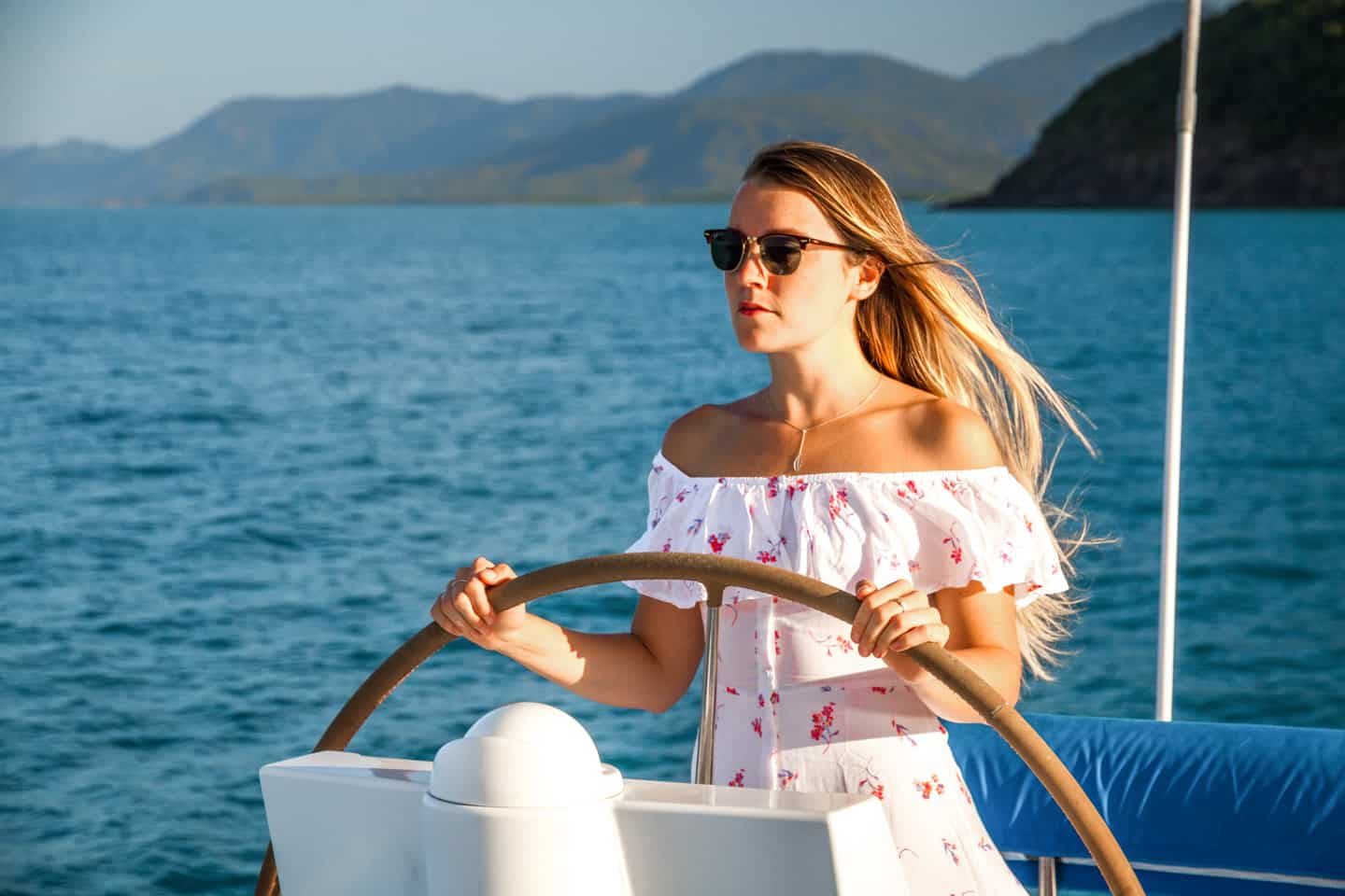 A girl at the steering wheel of a catamaran Port Douglas Queensland Australia
