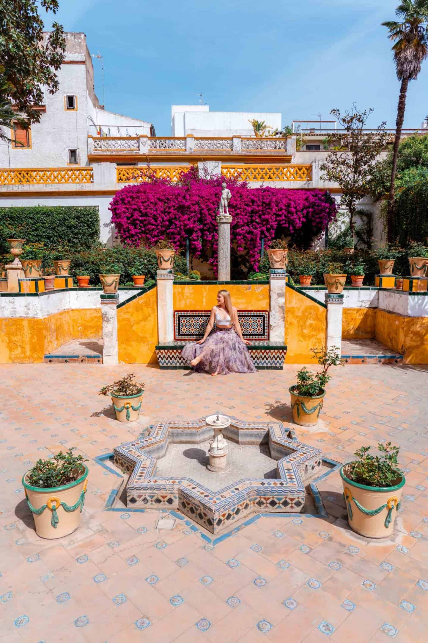 Girl in a purple skirt sat in the colourful garden of Casa de Pilatos Seville Spain