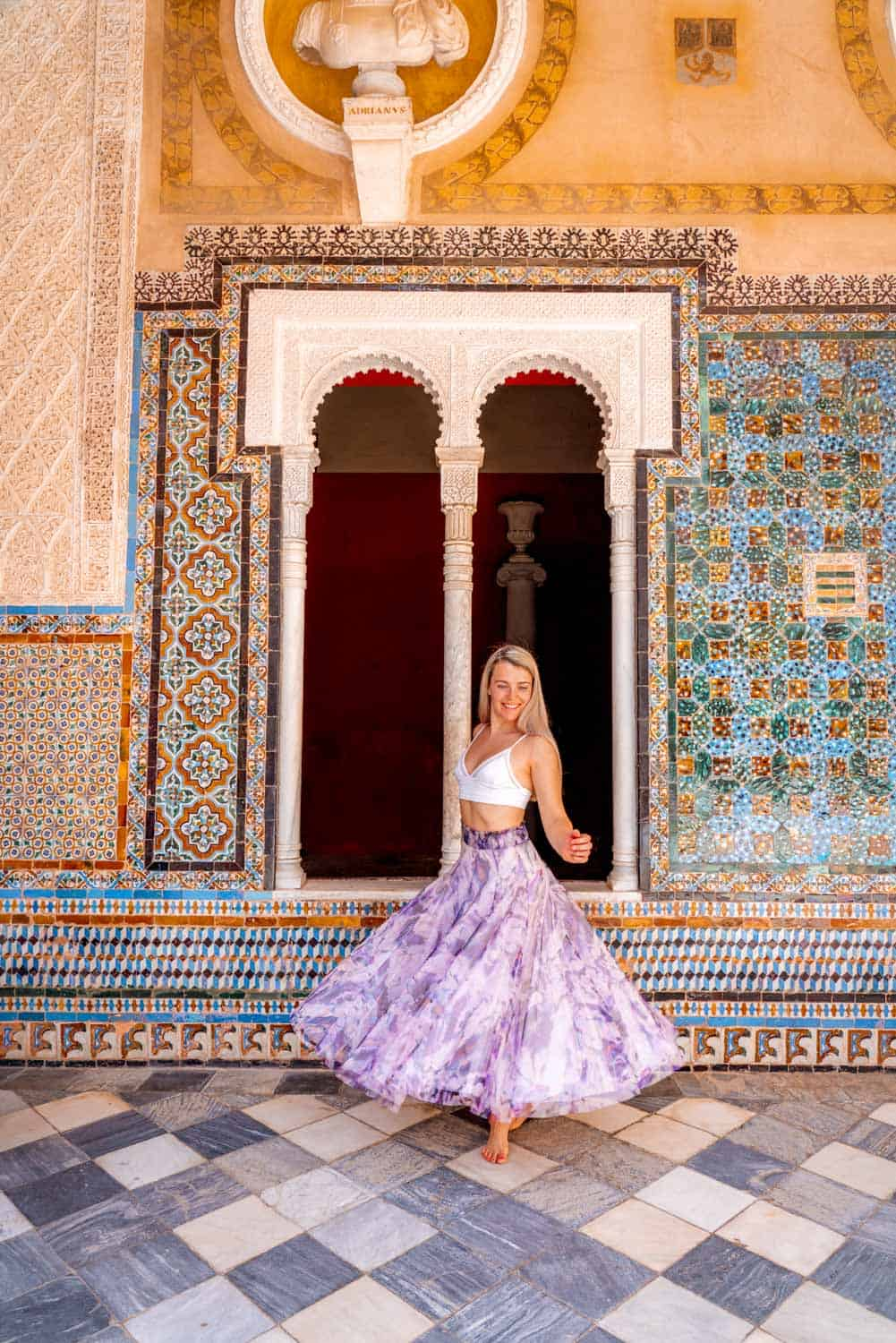 A girl in a skirt twirling in front of azulejo adorned archway in Casa de Pilatos Seville