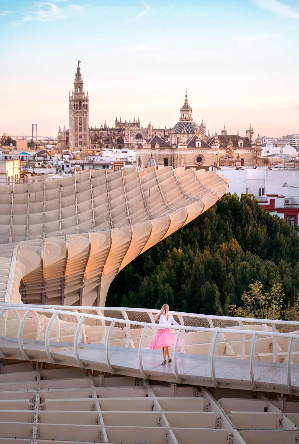 A girl in a pink skirt on the Metropol Parasol walkway overlooking the Seville Cathedral