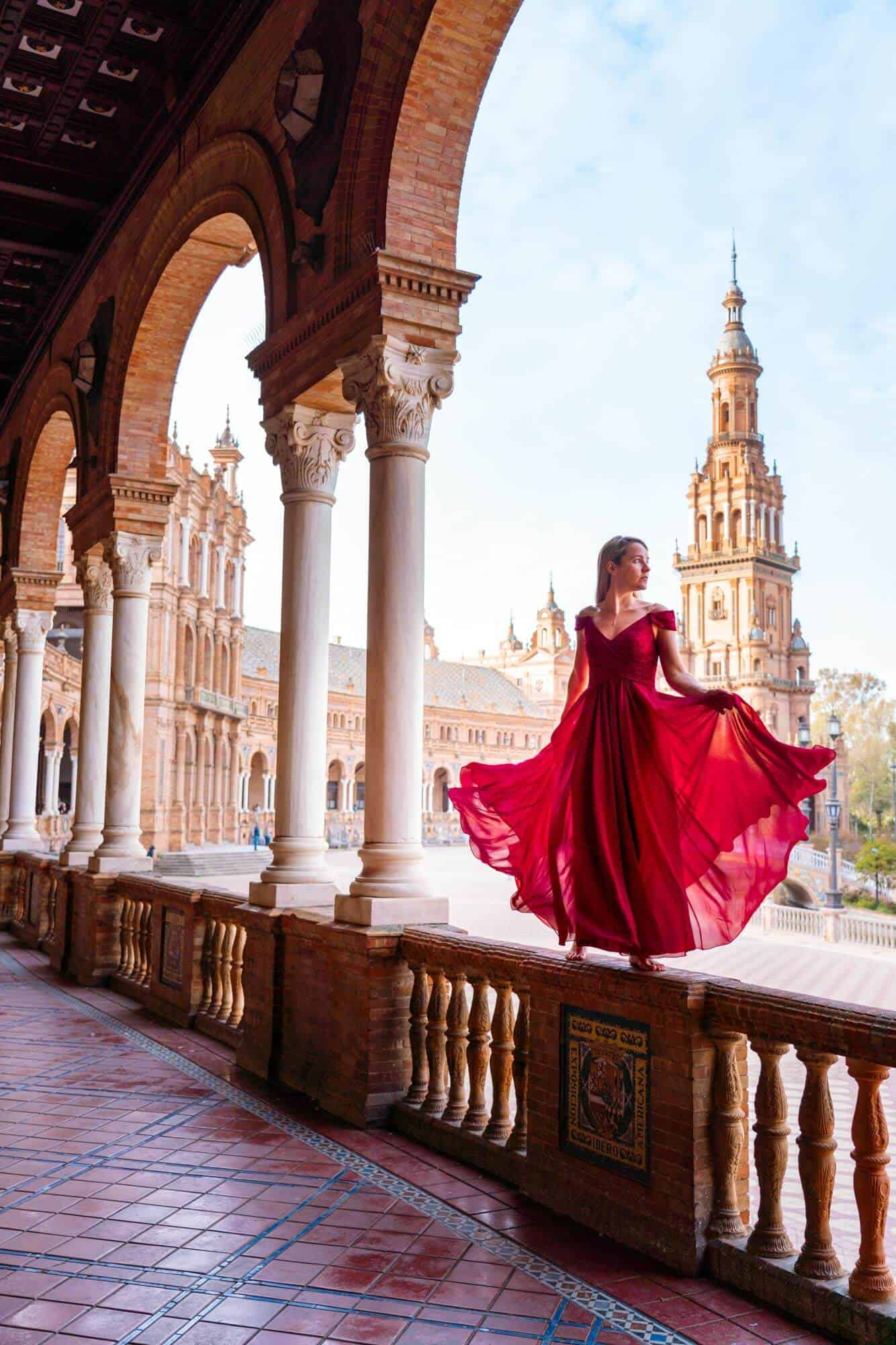 Girl in a red dress at Plaza de España capturing the perfect insta-worthy photo