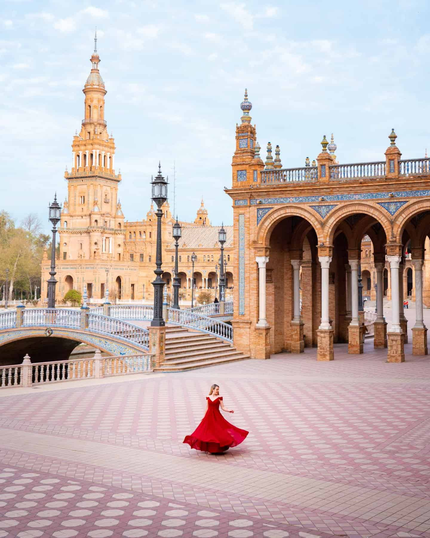 A girl in a red dress against the beautiful backdrop of Plaza de España Seville