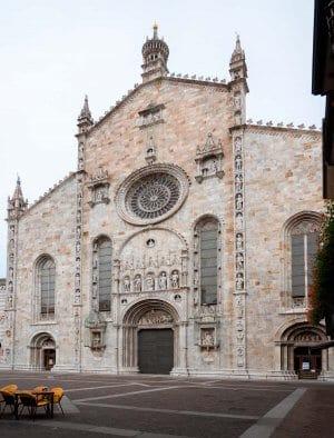 The white marble facade of Duomo di Como as seen from Piaza del Duomo, Lake Como Italy.  A must see on a day trip Milan to Lake Como.
