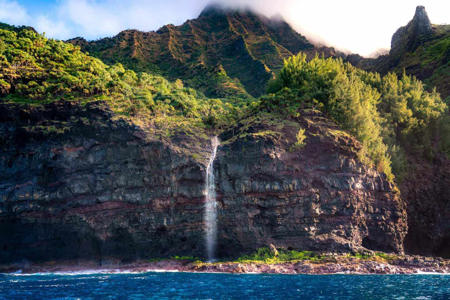 A waterfall spills from the cliffs of the Na Pali Coast on our Kauai itinerary.