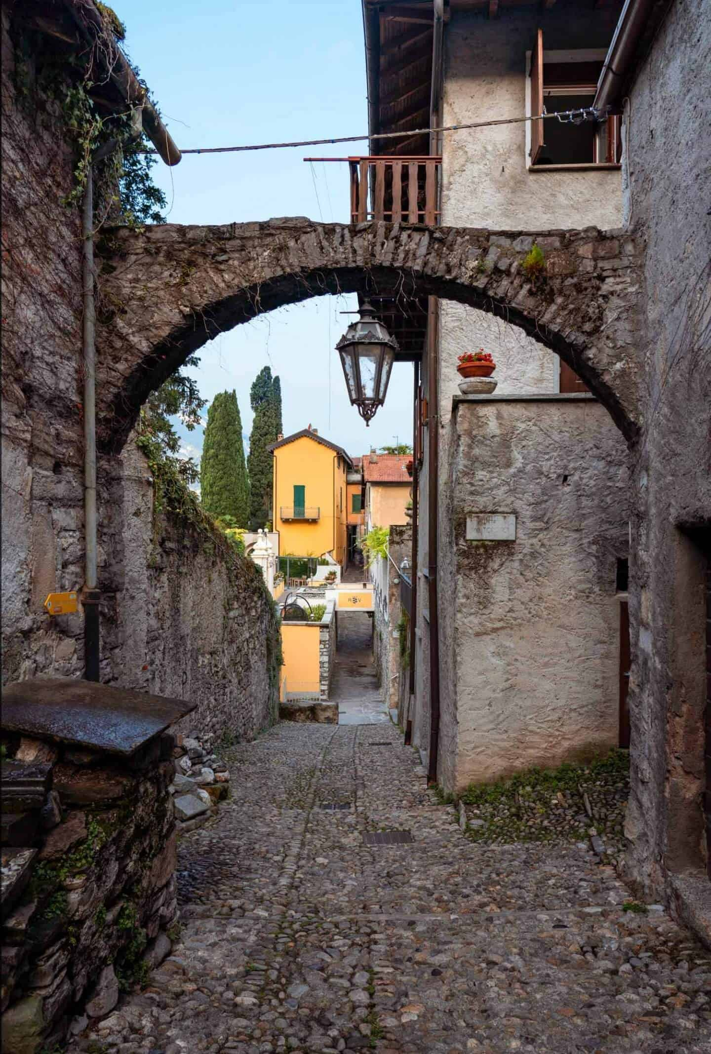A narrow, pretty alleyway with an arch and lantern over it in Varenna, Lake Como from Milan